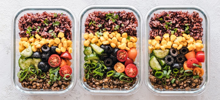 three plastic containers with foods
