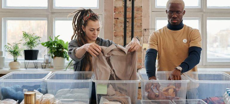 a man and a woman packing clothes in plastic containers to donate unwanted items in Los Angeles