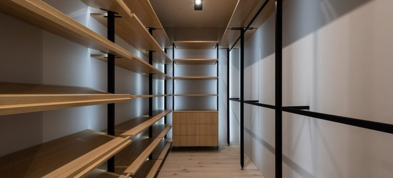 an empty closet with wooden shelves
