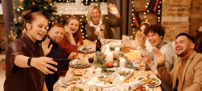 A girl who is taking a selfie of friends and family while having diner