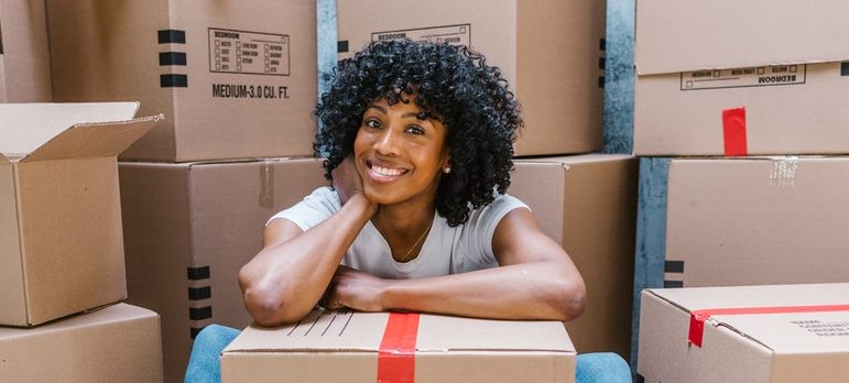 a woman sitting on the ground near carton boxes